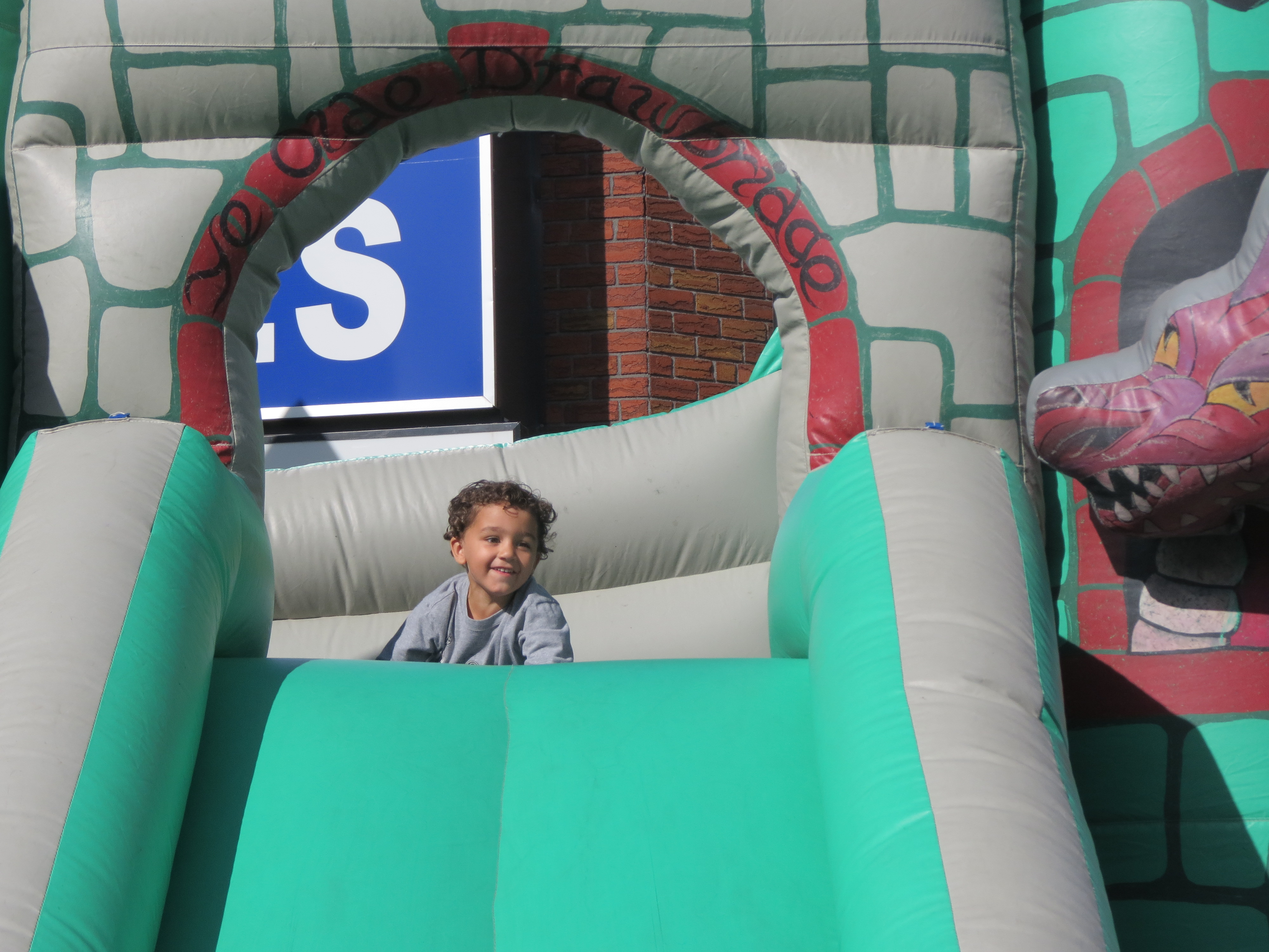 Isaiah Diaz, 3, of Ridgewood, peeks over the edge of one of a number of inflatable slides at the festivities.