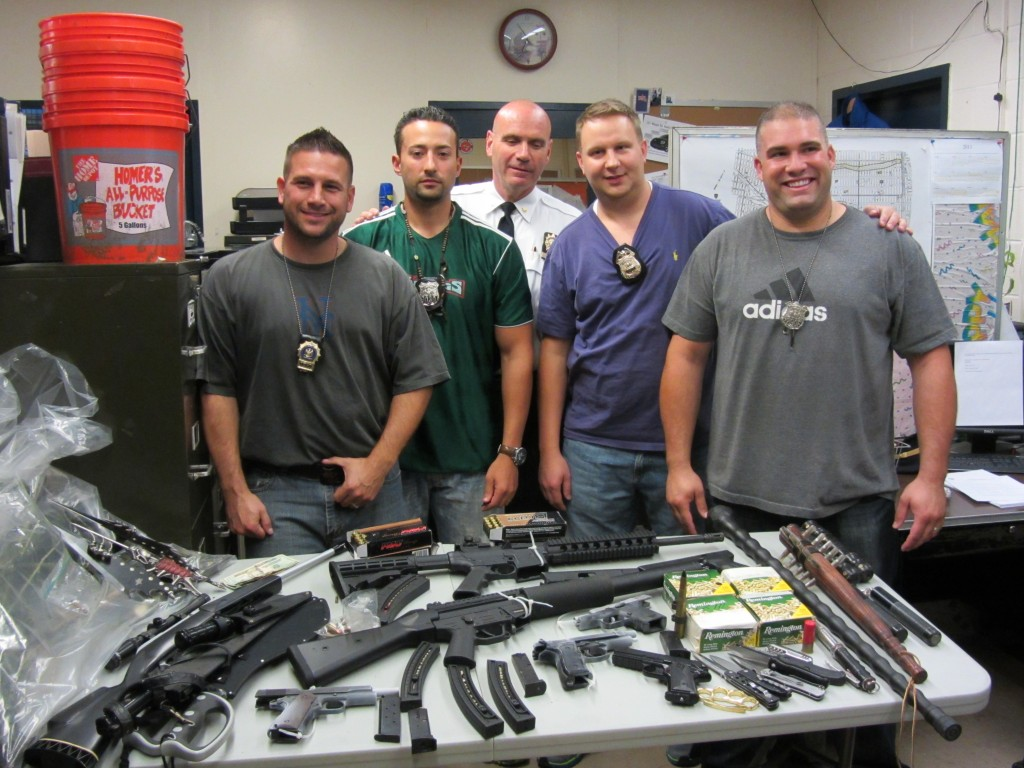There were lots of happy cops at the 106 after an investigation initiated by their field intelligence unit led them to a house which contained a large number of illegal guns, weapons and drugs. Pictured L to R:  Detective Nathaniel Taub, PO Thomas Scalise, Sgt. Joseph Muir and PO Sergio Silva. Photo Courtesy 106 Precinct