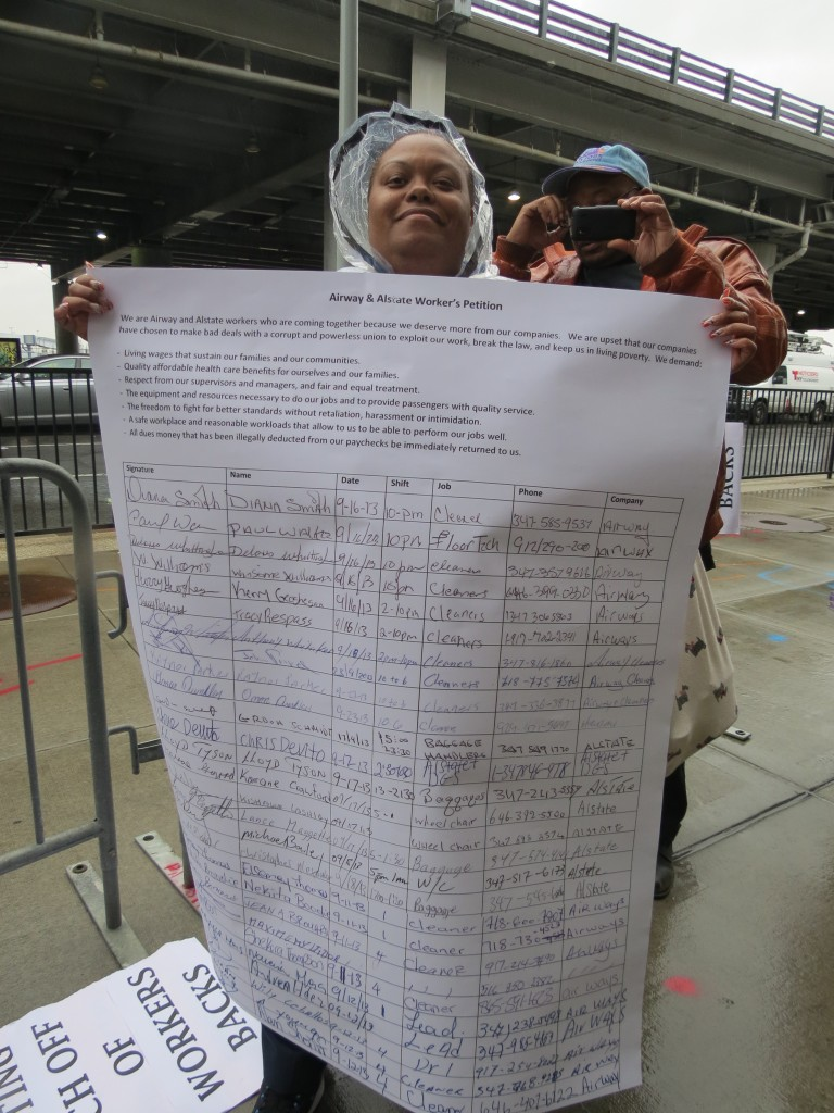 A protester outside JFK Airport last week shows off the hundreds of signatures from workers advocating for better working conditions. Anna Gustafson/The Forum Newsgroup