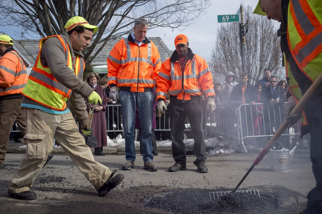 Mayor Bill de Blasio, center, works alongside a Department of Transportation crew to fix a pothole in Maspeth last Thursday. Photo courtesy Rob Bennett/NYC Mayor's Office