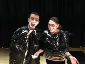 The classes of Maspeth High School history teachers Peter Casey, left, and Gabrielle Baker raised the most money for a drive to benefit typhoon victims in the Philippines - and students were rewarded by getting to see their instructors covered with whipped cream pie during a school comedy night.  photo courtesy Jessica Anderson/Maspeth High School