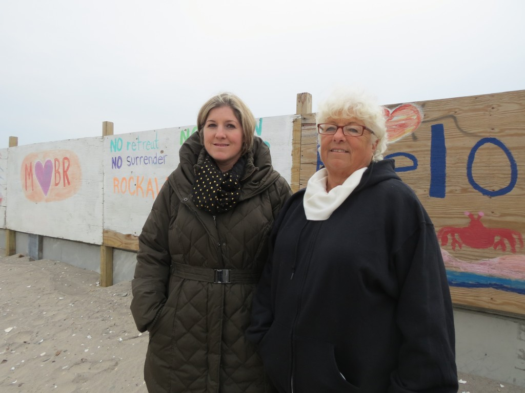Christine Schneider, left, and Leslie Mahoney stand before signs in the yard of their Belle Harbor home created after Hurricane Sandy. Photo by Anna Gustafson
