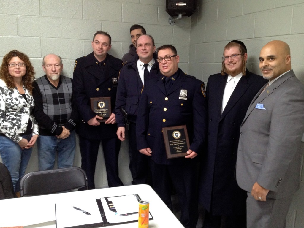 104th Precinct Capt. Charles Manson, center, awards March's top cops James Cullinan, third from left, and Vincent Chiarello, third from right, at the precinct community council meeting Tuesday evening. Photo by Phil Corso