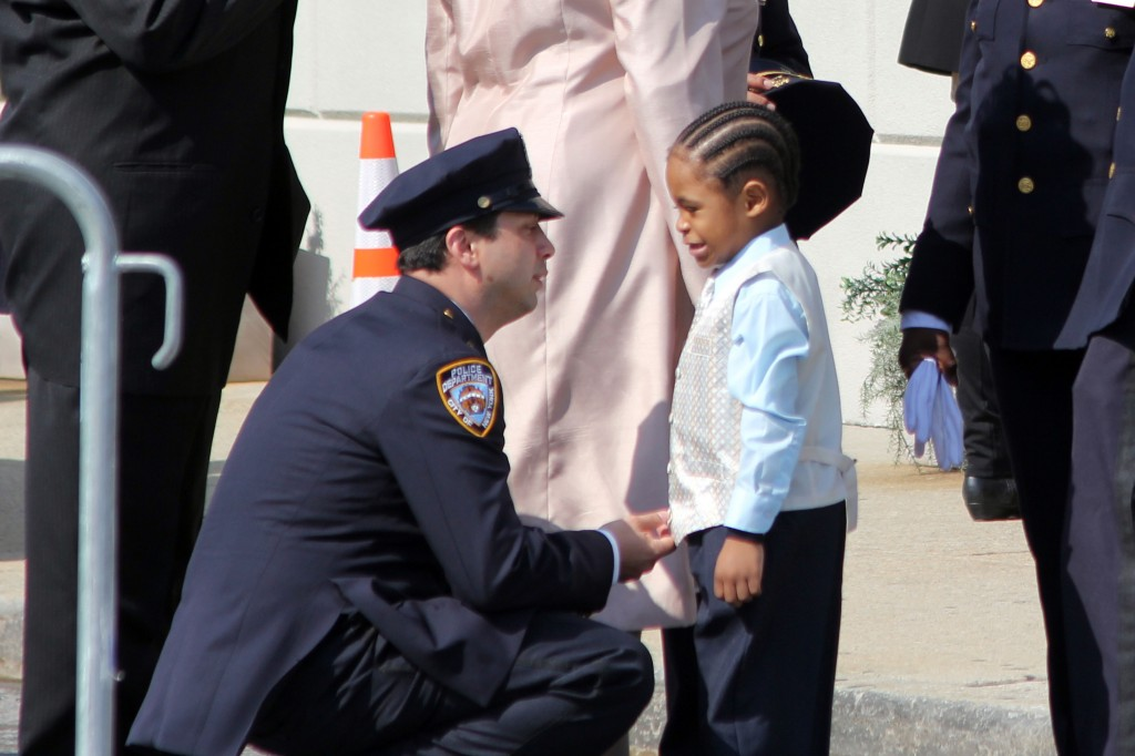 police officer spends time with one of the younger mourners at the funeral. Photo by Richard York