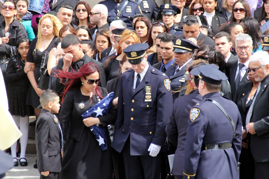 Officer Dennis Guerra's wife, Cathy, center, holds the U.S. flag presented to her at the funeral. Her youngest son, 7-year-old, Zachary, stands next to her. Photo by Richard York