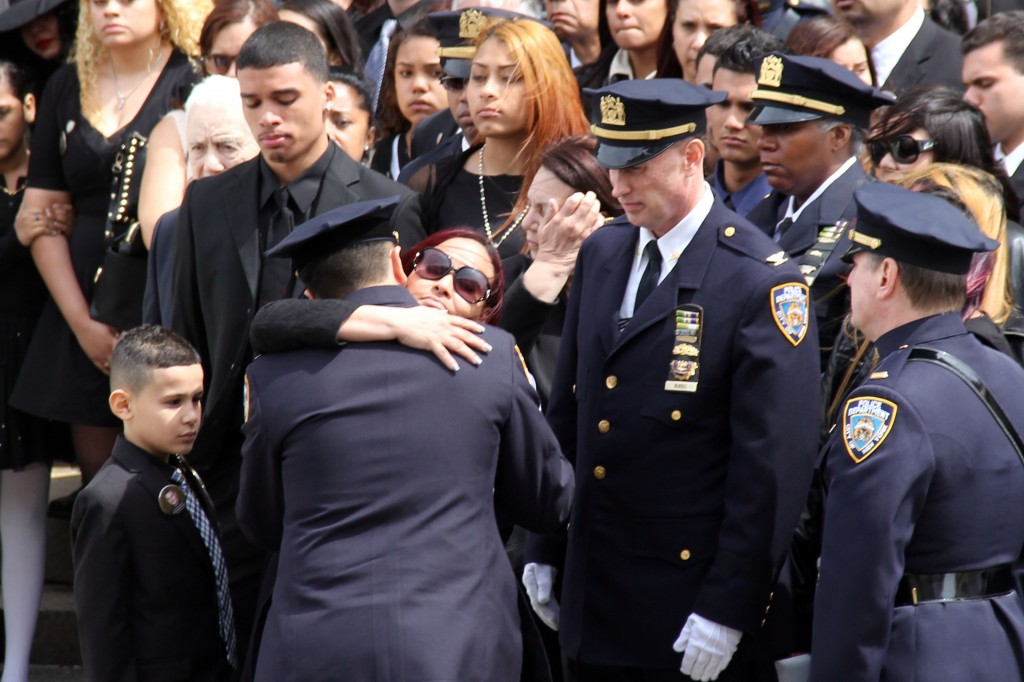 Officer Dennis Guerra's wife, Cathy, surrounded by her children and other family members, hugs a member of the NYPD at the funeral. Photo by Richard York