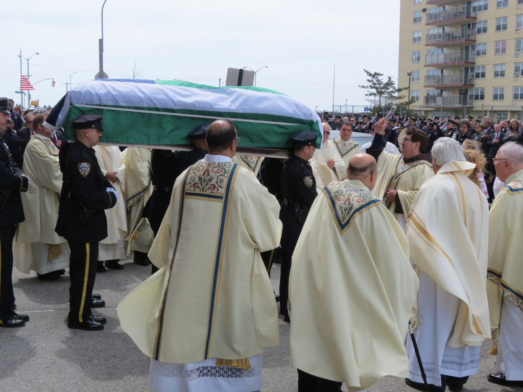 Officer Dennis Guerra's coffin is blessed outside the church. Photo by Anna Gustafson