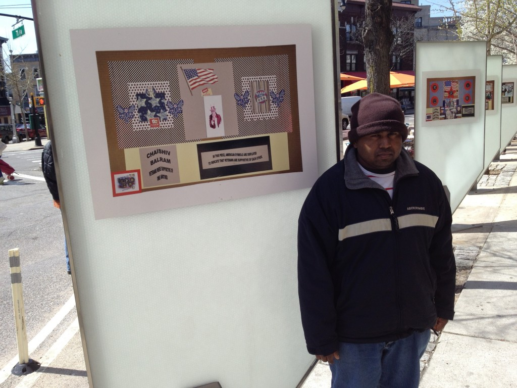 Chaishiv Balram, a veteran who served in Iraq, stands next to his artwork that was recently shown in Ridgewood. Photo by Phil Corso