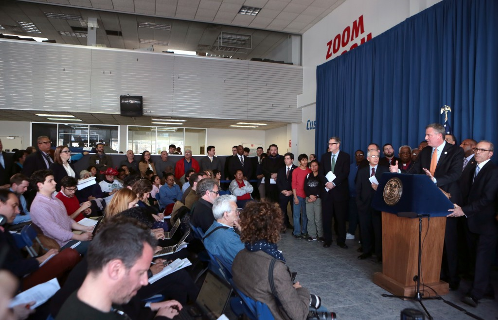 Mayor Bill de Blasio, at podium, vows at a press conference in Staten Island last week to bring relief to residents who have been struggling for nearly 18 months since Hurricane Sandy hit New York. Photo courtesy Ed Reed/NYC Mayor's Office