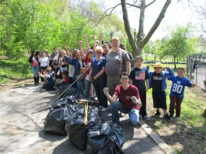 Volunteers celebrate the conclusion of the clean-up with some of the bags of leaves and debris they had gathered. Note that the long line of black garbage bags in the background.  Photo courtesy Josephine Wendell