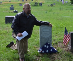 Sean Walsh, a former U.S. Marine, kneels by a new military headstone that was placed in the Evergreens Cemetery for his third great-grandfather, Lt. John Charles Walsh, who fought in the Union Army during the Civil War.  Photo by Caroline Roswell