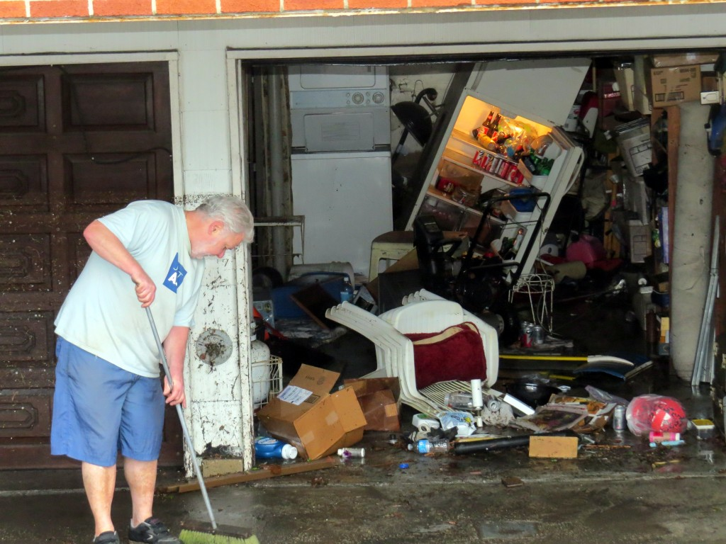 A Lindenwood resident cleans out his garage following last Wednesday's massive rainstorm.  Photo by Robert Stridiron