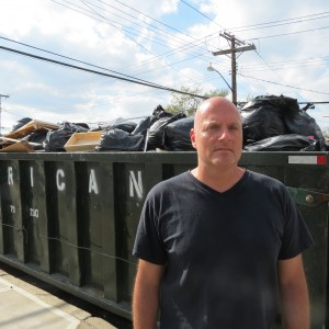 James Noto stands in front of the garbage bin containing many of the items that he and his family had to throw out after a flood destroyed their garage and basement in their Lindenwood home.  Photo by Anna Gustafson