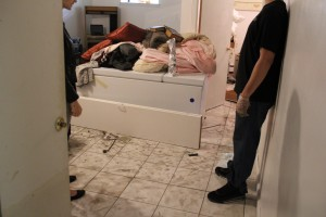 Lindenwood residents clean up a home hit by flooding last Wednesday.  Photo by Richard York