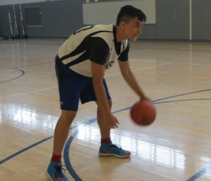 Paolo Tamer, student/ basketball athlete dribbles the basketball as he practices his shooting techniques in the school's gym.  Photo by Debbie Cohen