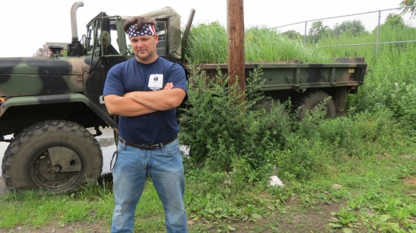 Howard Beach resident Paul Marcel stands with the army truck he used to rescue 120 people during Hurricane Sandy. Recently, some neighbors have complained about the truck being abandoned in a parking space on 78th Street. Photo by Ashley Helms