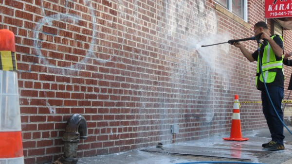 Magic Touch Cleaning & Maintenance worker power-washes graffiti off a small business's wall on 101st Street.  Photo by Michael V. Cusenza