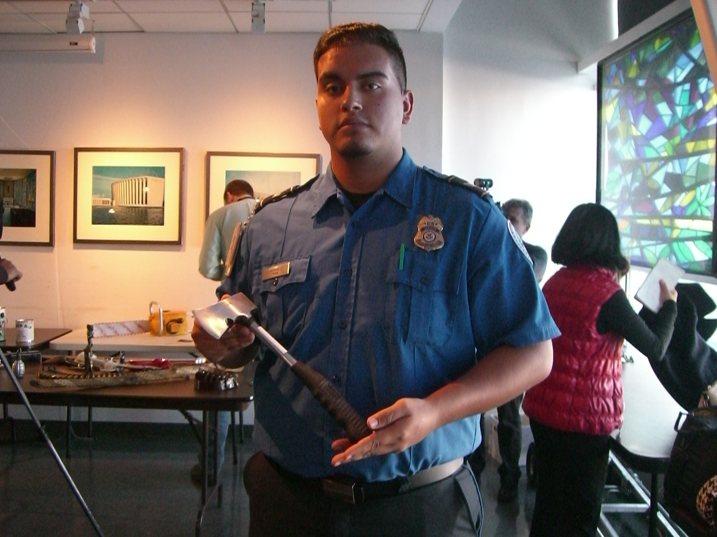 transportation security officer camilo bernal displays a hatchet that was surrendered by a passenger at a - Transportation Security Officer