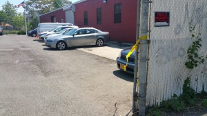 Remnants of crime scene tape dangling from the entrance gate of an Ozone Park armored car depot are a reminder of what happened on Monday morning. Forum Photo by Michael V. Cusenza.