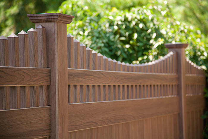 A sloped picket design adds an elegant touch to the gated sections of the fence.