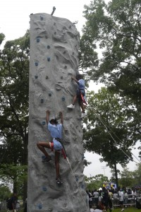 A boy and a girl race to the top of a rock wall at the 25th annual Patrol Borough Queens South Harmony Picnic at Roy Wilkins Park in Jamaica.  Forum Photo by Greg Zwiers