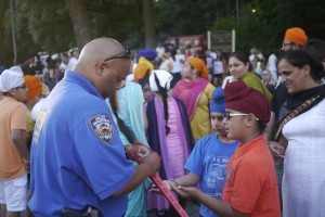 A Community Affairs officer hands out tickets to eager children Tuesday evening at the Buddy Memorial Monument in Forest Park.  Forum Photo by Greg Zwiers
