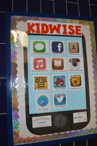 A kid-friendly KidWise poster in the hallway at Basie Beacon 72 displays services offered by the clinic in the form of smartphone app icons.  Forum Photo by Eugénie Bisulco