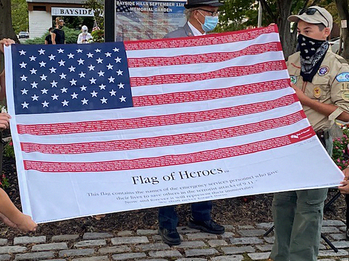 Photo Courtesy of Rep. Meng's Office Boy Scouts unfurled the Flag of Heroes during the Sept. 11 observance in Bayside Hills organized by the Bayside Hills Civic Association.