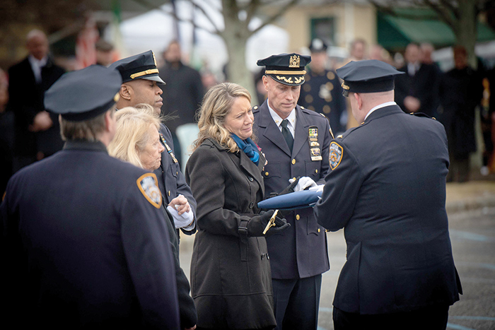 File Photo Simonsen's Widow, Leanne, accepts the American flag that was draped over the fallen cop's casket.